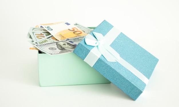 Abra a caixa de presente com uma grande moeda de ouro dentro da mesa. conceito de presente de dinheiro.