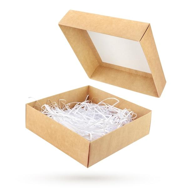 Abra a caixa de presente de papelão marrom com papel picado isolado na superfície branca