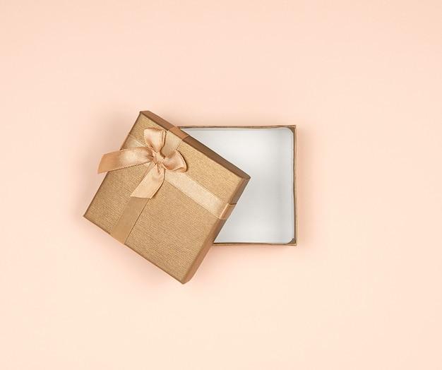 Abra a caixa de presente dourada com um laço no bege