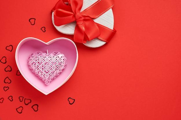 Abra a caixa de presente em forma de coração com uma fita vermelha em um fundo vermelho. cartão postal do conceito de dia dos namorados. vista do topo.