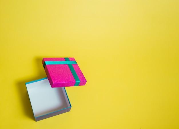 Abra a caixa de presente em um espaço amarelo. caixa de presente rosa com fita turquesa. liquidação de verão.