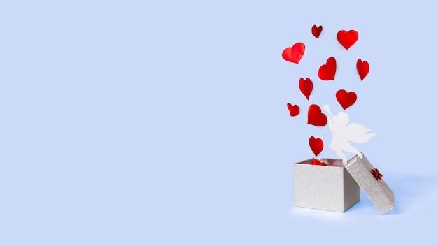 Abra a caixa de presente prata com corações e cupido voando. levitação. feliz dia dos namorados.