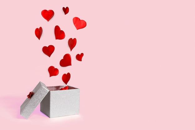 Abra a caixa de presente prata com corações voando. levitação. feliz dia dos namorados.