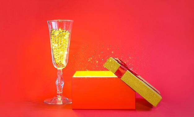 Abra a caixa de presente vermelha com brilho dourado e taça de champanhe com contas de bolha