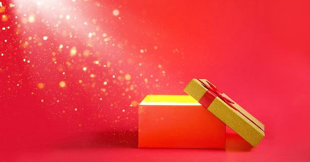 Abra a caixa de presente vermelha com um brilho dourado e glitter em um fundo vermelho