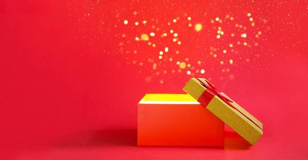 Abra a caixa de presente vermelha com um brilho dourado em um fundo vermelho