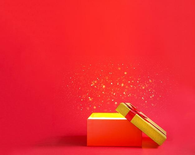 Abra a caixa de presente vermelha com um laço com um brilho dourado