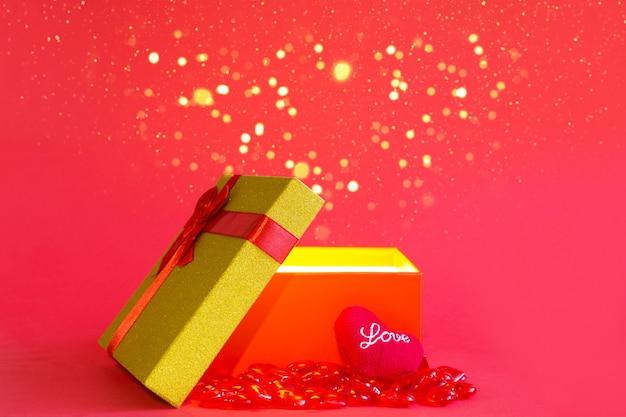 Abra a caixa de presente vermelha com um laço e um coração mole