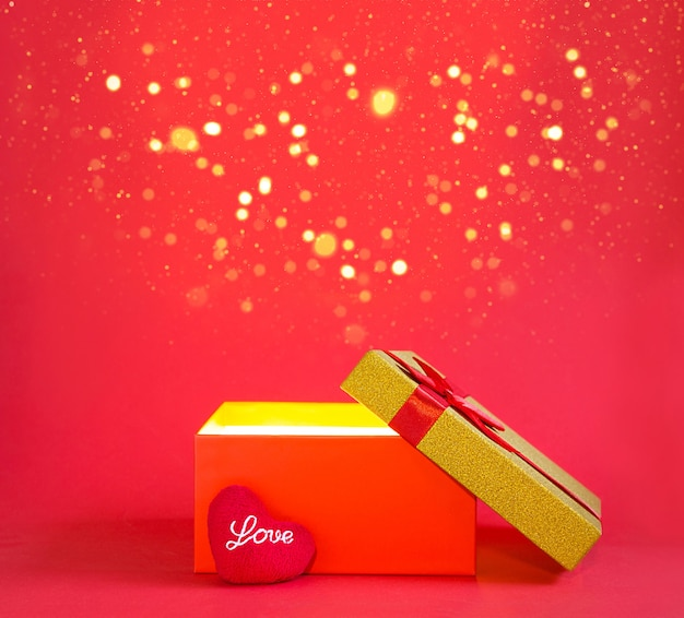 Abra a caixa de presente vermelha e um coração mole com a inscrição amor em um fundo vermelho