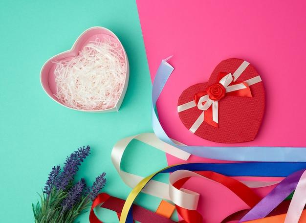 Abra a caixa de presente vermelha em forma de coração com um laço verde rosa