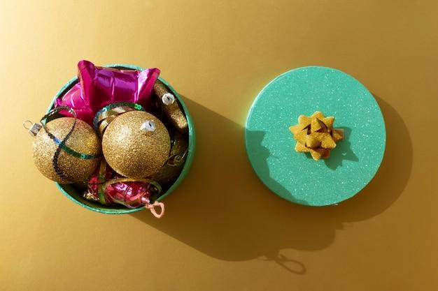 Abra a caixa de purpurina com decorações de natal em um fundo dourado como pano de fundo festivo de natal