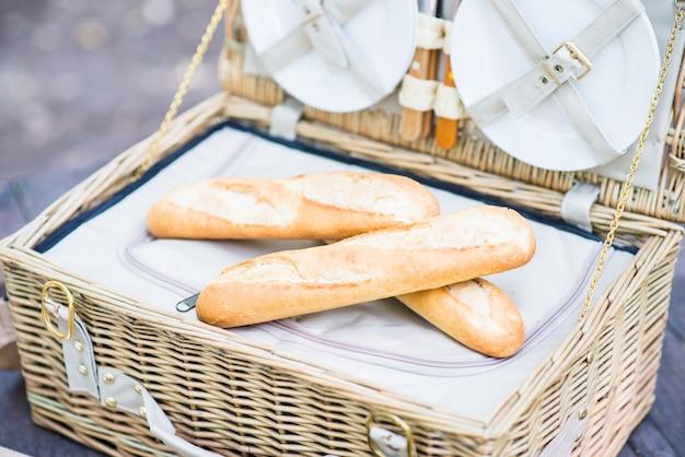 Abra a cesta do piquenique com pão para dentro sobre uma tabela de madeira no parque.