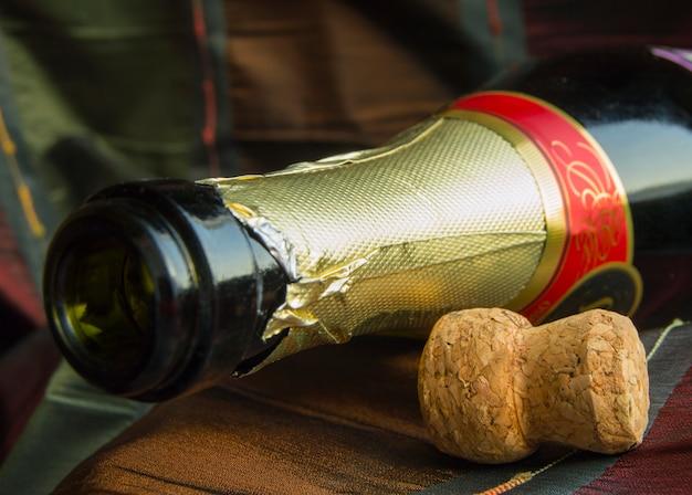Abra a garrafa de champanhe e a rolha na mesa com uma toalha de mesa