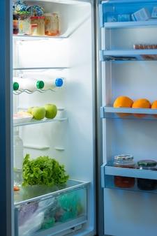 Abra a geladeira na cozinha à noite