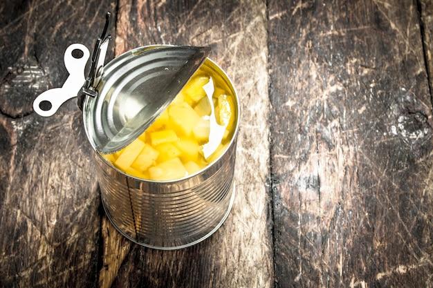 Abra a lata com abacaxi em conserva em um fundo de madeira