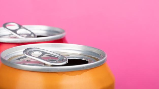 Abra a lata de cerveja vermelha e amarela, close-up no fundo rosa