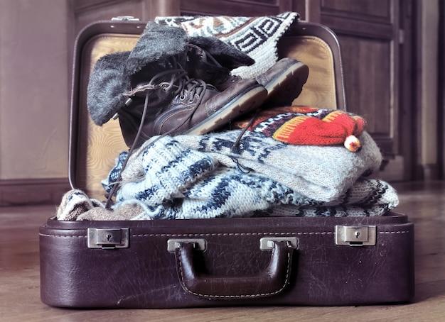 Abra a mala cheia de roupas quentes no chão