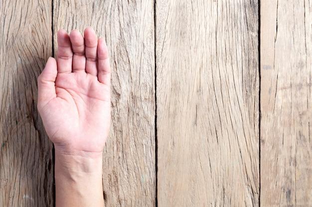 Abra a mão masculina da ásia em fundo de madeira.