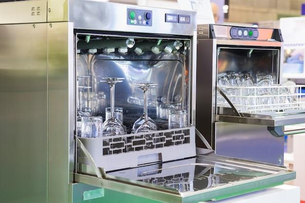 Abra a máquina de lavar louça com vidro limpo, copos, pratos e pratos, foco seletivo