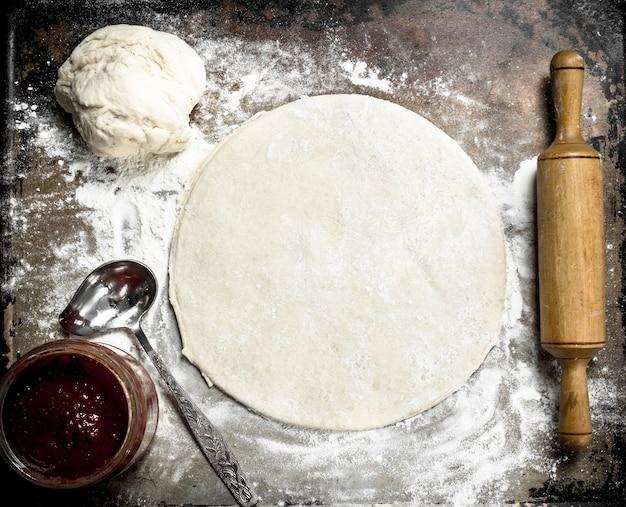 Abra a massa para pizza. sobre um fundo rústico.