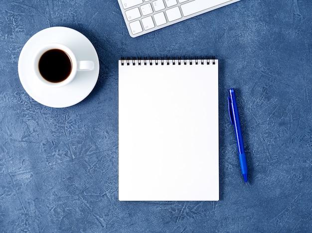 Abra a página branca limpa de bloco de notas, caneta e xícara de café na mesa de pedra azul escura envelhecida, vista superior