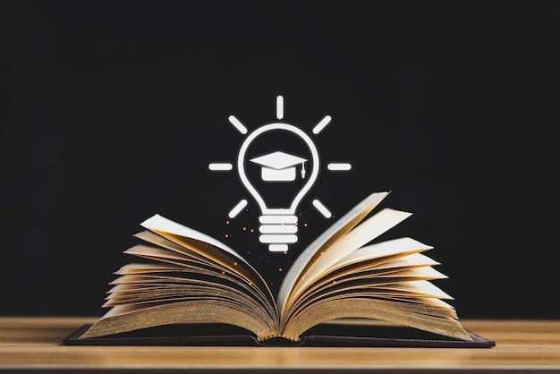 Abra a página do meio do livro e o símbolo do boné de formatura na mesa de madeira isolada no fundo preto.