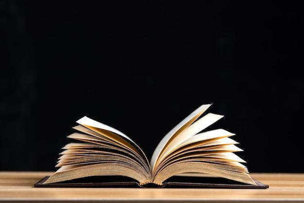 Abra a página do meio do livro na mesa de madeira isolada no fundo preto.