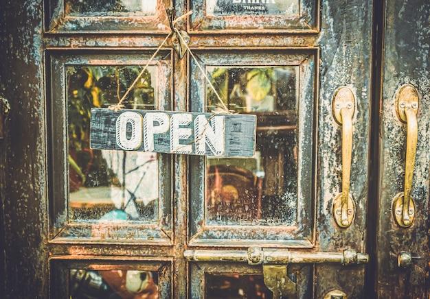 Abra a placa pendurada na porta vintage