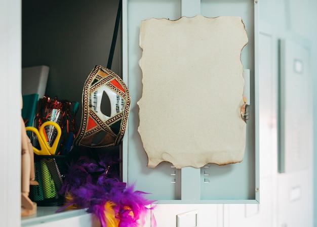 Abra a porta do armário com a página queimada; mascara de carnaval; tesoura e boa de penas