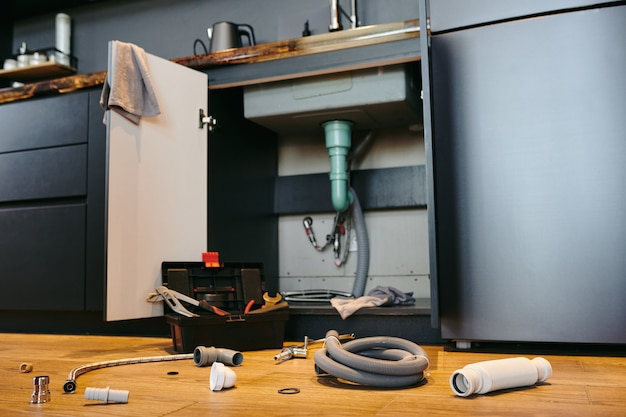 Abra a porta do armário sob a pia da cozinha, caixa de ferramentas e equipamento de encanamento