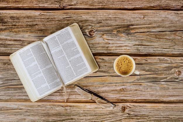Abra as leituras da manhã da bíblia em cima de uma mesa com uma xícara de café e óculos