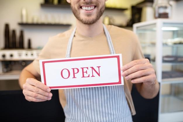 Abra, assine. placa branca com inscrição vermelha aberta nas mãos de um homem de avental, a parte inferior do rosto é visível