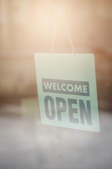 Abra e dê boas-vindas ao sinal largo através do vidro da janela para deixar clientes saber