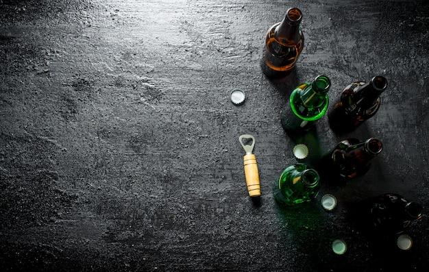 Abra garrafas de cerveja de vidro e abridor. sobre fundo preto rústico