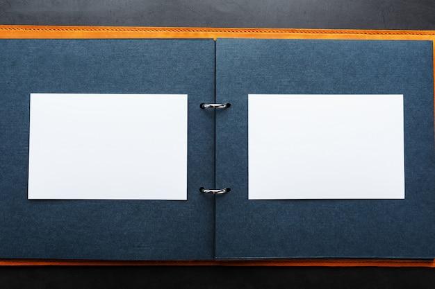 Abra o álbum de fotos com espaço vazio para fotos, quadros brancos em papel preto. a capa do álbum é feita de couro genuíno artesanal marrom
