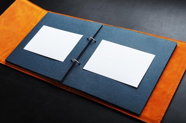 Abra o álbum de fotos com espaço vazio para fotos, quadros brancos em papel preto. a capa do álbum é feita de couro genuíno artesanal marrom.