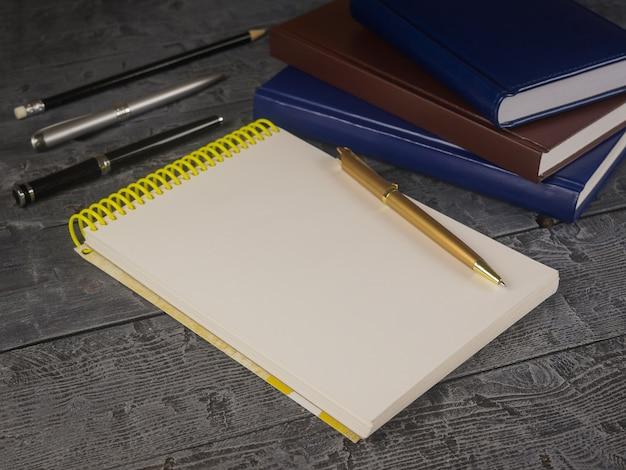 Abra o bloco de notas, caneta, lápis e livro sobre uma mesa de madeira preta.