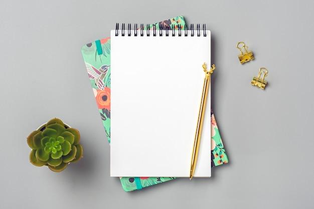 Abra o bloco de notas com caneta dourada e caderno espiral na mesa