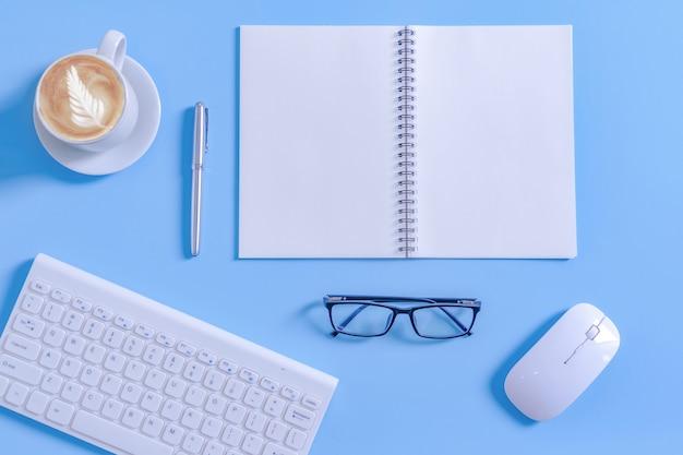 Abra o bloco de notas com equipamento de escritório e xícara de café com leite na mesa de trabalho.