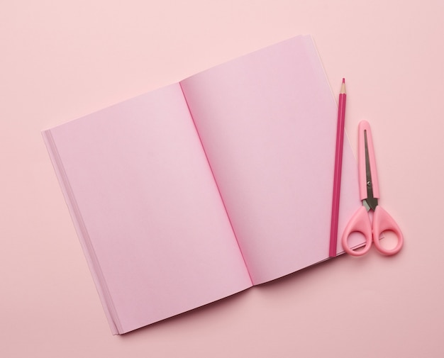 Abra o bloco de notas com folhas rosa em branco e tesoura em fundo rosa