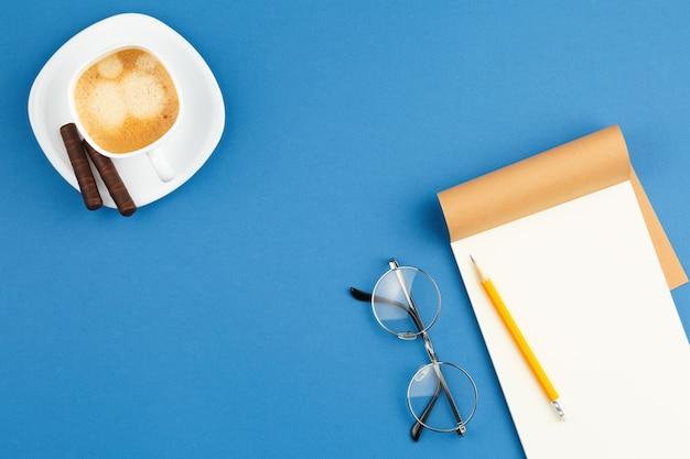 Abra o bloco de notas com uma xícara de café com lápis