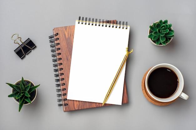 Abra o bloco de notas com uma xícara de café e caneta dourada