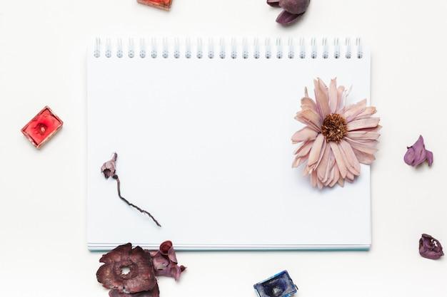 Abra o bloco de notas em branco com flores secas e potes de tinta aquarela na vista superior branca