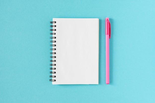 Abra o bloco de notas em espiral em um azul, o caderno e a caneta estão no papel textural
