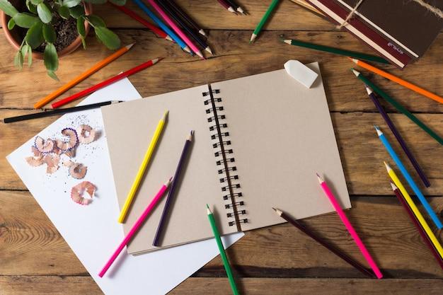 Abra o bloco de notas, folha de papel puro, lápis de cor sobre a mesa de madeira velha. vista plana, vista superior
