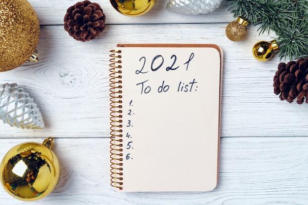 Abra o bloco de notas para a lista de tarefas com decorações festivas em uma superfície plana de madeira, vista de cima