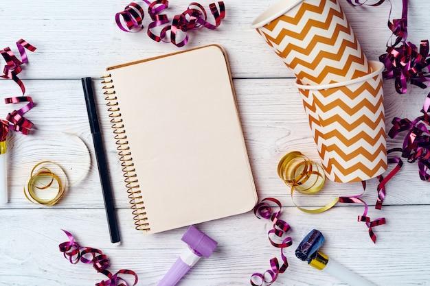 Abra o bloco de notas para a lista de tarefas com decorações festivas na vista superior da superfície de madeira
