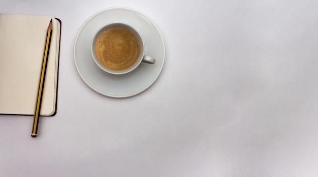 Abra o caderno com caneta e xícara de café em fundo branco. conceito de trabalho. vista do topo. postura plana. copie o espaço.