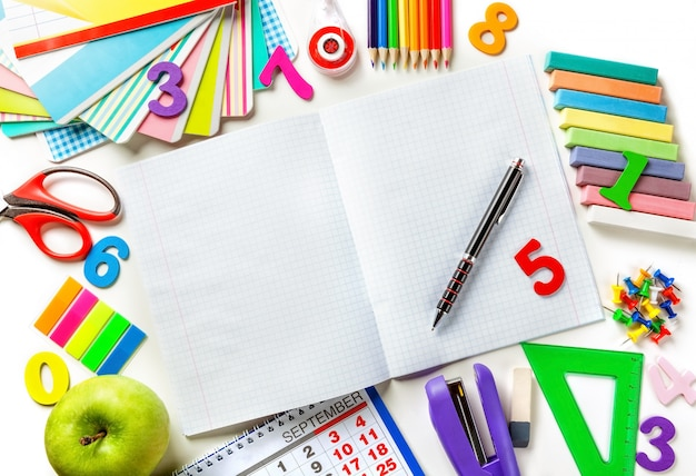 Abra o caderno da página em branco com uma caneta no centro do quadro. vários materiais de escritório.