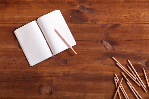 Abra o caderno de anotações com lápissonbrownwoodendesk, topview, flatlay